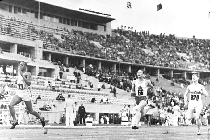 FILE - In this Aug. 4, 1936, file photo, American athlete Jesse Owens, left, breaks the tape in a record time of 21.1 seconds in the elimination heats of the men's 200-meter race at the Olympic Games race in Berlin, Germany. Canada's Lee Orr, center, finished second. (AP Photo/File)