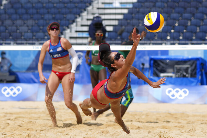 Sarah Sponcil, right, of the United States, stretches out for the ball as teammate Kelly Claes looks on during a women's beach volleyball match against Kenya at the 2020 Summer Olympics, Thursday, July 29, 2021, in Tokyo, Japan. (AP Photo/Petros Giannakouris)