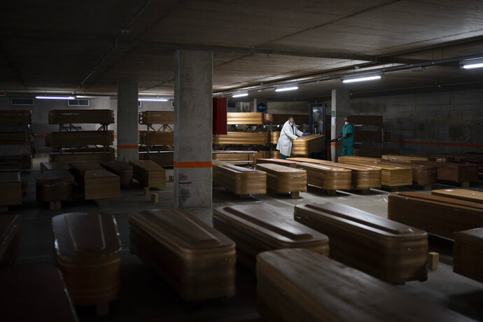 Coffins carrying the bodies of people who died of coronavirus are stored waiting to be buried or incinerated in an underground parking lot at the Collserola funeral home in Barcelona, Spain, April 2, 2020. (AP Photo/Felipe Dana)