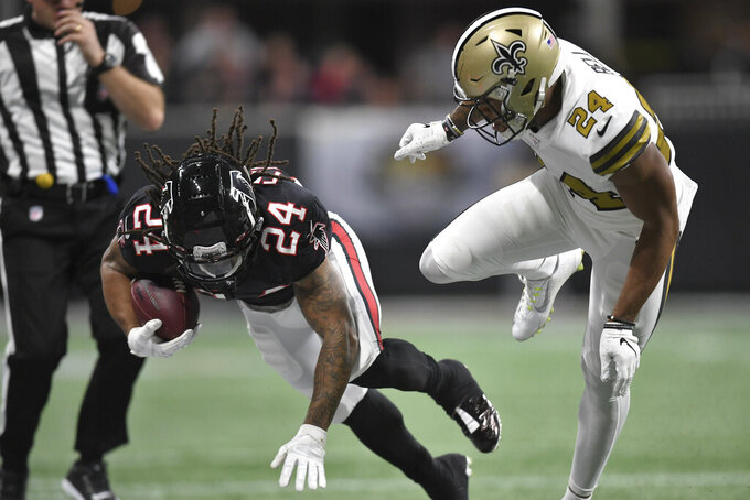 New Orleans Saints strong safety Vonn Bell (24) hits Atlanta Falcons running back Devonta Freeman (24) during the first half of an NFL football game, Thursday, Nov. 28, 2019, in Atlanta. (AP Photo/Danny Karnik)