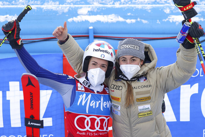 Italy's Marta Bassino, left, third in an alpine ski, women's World Cup giant slalom, celebrates with Italy's Sofia Goggia, in San Vigilio di Marebbe, Italy, Tuesday, Jan. 26, 2021. (AP Photo/Alessandro Trovati)