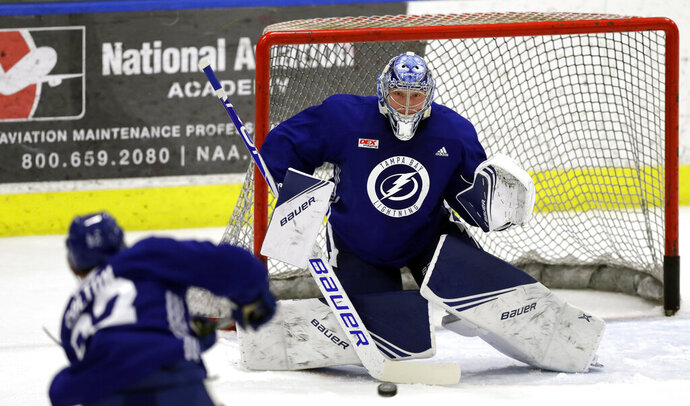 FILE - In this Sept. 13, 2019, file photo, Tampa Bay Lightning goaltender Andrei Vasilevskiy (88) eyes a shot during the first day of training camp, in Brandon, Fla. Fresh off finishing 21 points ahead of the NHL last regular season and going four and out in the playoffs, the Lightning are again Stanley Cup favorites and the team to beat in an ever-improving the Eastern Conference. (AP Photo/Chris O'Meara, File)