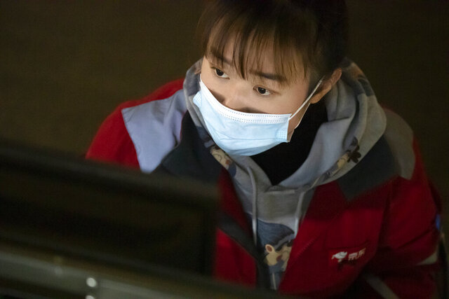 An employee looks at a computer terminal as she monitors an automated parcel handling line at a warehouse for online retailer JD.com in Beijing, Wednesday, Nov. 11, 2020. Chinese consumers spent over a hundred billion dollars during this year's Singles' Day shopping festival, signaling a rebound in consumption as China recovers from the coronavirus pandemic and a battering of the economy. (AP Photo/Mark Schiefelbein)