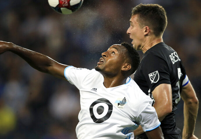 Minnesota United forward Mason Toye, left, heads the ball next to Sporting Kansas City defender Matt Besler during the first half of an MLS soccer match in Kansas City, Kan., Thursday, Aug. 22, 2019. (AP Photo/Orlin Wagner)