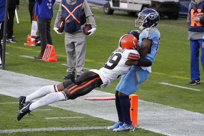 Tennessee Titans wide receiver Cameron Batson, right, catches a touchdown pass as he is hit by Cleveland Browns cornerback Terrance Mitchell (39) in the second half of an NFL football game Sunday, Dec. 6, 2020, in Nashville, Tenn. (AP Photo/Ben Margot)