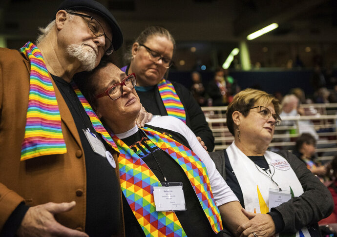 FILE - In this Feb. 26, 2019 file photo, Ed Rowe, left, Rebecca Wilson, Robin Hager and Jill Zundel, react to the defeat of a proposal that would allow  LGBTQ clergy and same-sex marriage within the United Methodist Church at the denomination's 2019 Special Session of the General Conference in St. Louis, Mo. The 16 United Methodist bishops and advocacy group leaders who negotiated the recent proposal to split the denomination met on Monday, Jan. 13, 2020, to explain their reasoning at an event that was streamed live by United Methodist News Service. (AP Photo/Sid Hastings, File)