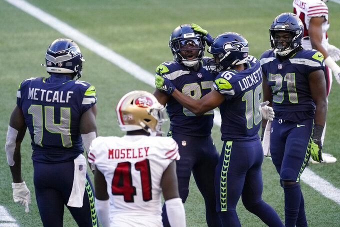 Seattle Seahawks' David Moore, center, celebrates with Tyler Lockett (16) DeeJay Dallas (31) and DK Metcalf (14) after Moore scored a touch down against the San Francisco 49ers during the second half of an NFL football game, Sunday, Nov. 1, 2020, in Seattle. The Seahawks won 37-27. (AP Photo/Elaine Thompson)