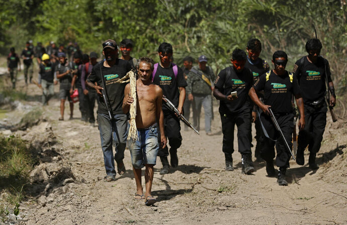 Altemir Freitas Mota carries a tool used in cutting down trees as he leads Tenetehara Indigenous men from the Ka'Azar, or Forest Owners, to his group's campsite after he was apprehended for illegal logging on the Alto Rio Guama reserve in Para state, near the city of Paragominas, Brazil, Tuesday, Sept. 8, 2020. Three Tenetehara Indigenous villages are patrolling to guard against illegal logging, gold mining, ranching, and farming on their lands, as increasing encroachment and lax government enforcement during COVID-19 have forced the tribe to take matters into their own hands. (AP Photo/Eraldo Peres)