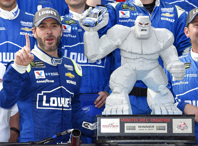 FILE - In this June 4, 2017, file photo, Jimmie Johnson, left, poses with the trophy in Victory Lane after he won a NASCAR Cup series auto race at Dover International Speedway in Dover, Del. Jimmie Johnson has a track-record 11 wins at Dover International Speedway. He'll have to win No. 12 to guarantee a playoff spot and he has two shots this weekend when the NASCAR Cup series races on Saturday and Sunday. (AP Photo/Nick Wass, File)