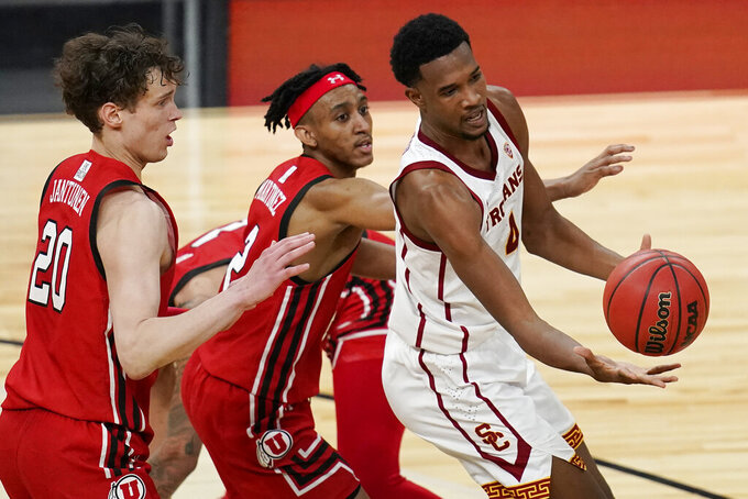 Southern California's Evan Mobley, right, passes around Utah's Mikael Jantunen, left, and Ian Martinez during the first overtime of an NCAA college basketball game in the quarterfinal round of the Pac-12 men's tournament Thursday, March 11, 2021, in Las Vegas. (AP Photo/John Locher)