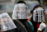 Activists wearing protective face shields as a precaution against the new coronavirus outbreak attend a small protest outside the parliament in Jakarta, Indonesia, Tuesday, July 14, 2020. About a dozen activists staged the protest opposing the government's omnibus bill on job creation that was intended to boost economic growth and create jobs, saying that it undermined labor rights and environmental protection. (AP Photo/Dita Alangkara)