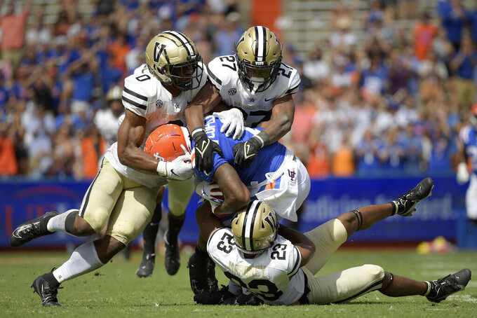 Florida wide receiver Jacob Copeland (1) is tackled by Vanderbilt linebacker Anfernee Orji (0), safety Brendon Harris (27) and cornerback Jaylen Mahoney (23) after catching a pass during the second half of an NCAA college football game, Saturday, Oct. 9, 2021, in Gainesville, Fla. (AP Photo/Phelan M. Ebenhack)
