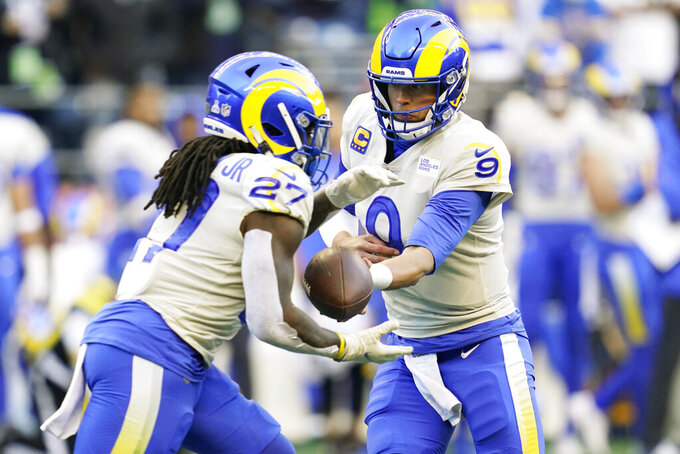 Los Angeles Rams quarterback Matthew Stafford (9) hands off to running back Darrell Henderson (27) during the first half of an NFL football game against the Seattle Seahawks, Thursday, Oct. 7, 2021, in Seattle. (AP Photo/Elaine Thompson)