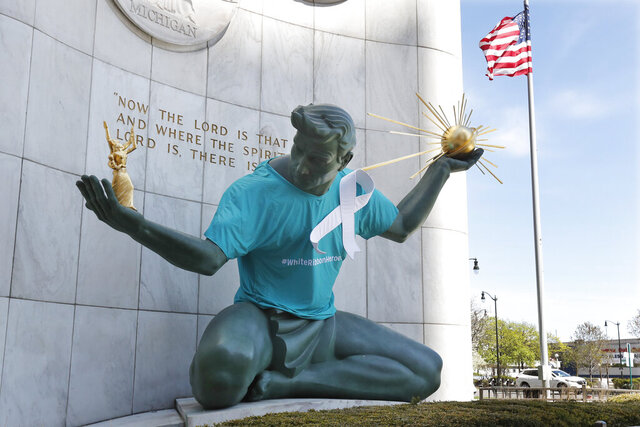 The Spirit of Detroit statue by Marshall Fredericks wears a white ribbon to honor essential workers, first responders and health care workers, Wednesday, May 6, 2020, in Detroit. (AP Photo/Carlos Osorio)