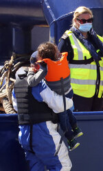A Border Force officer helps a young girl from a Border Force vessel as a group of people thought to be migrants are brought into the port city of Dover, England, from small boats, Friday Aug. 7, 2020. The British government says it will strengthen border measures as calm summer weather has prompted a record number of people to attempt the risky sea crossing in small vessels, from northern France to England. (Gareth Fuller/PA via AP)