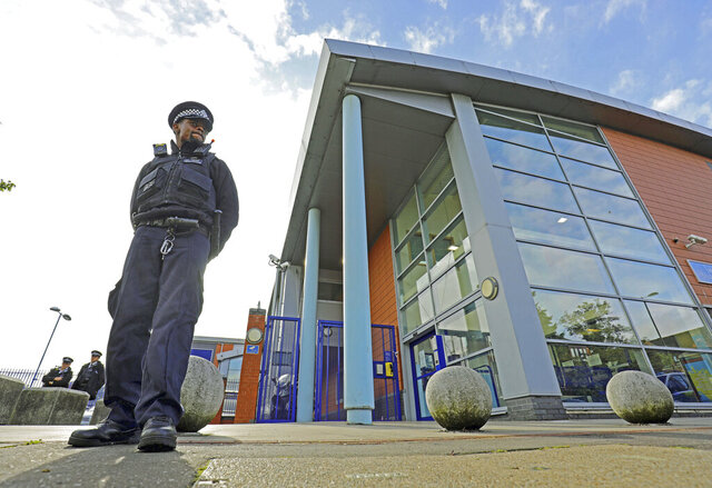 A police officer stands outside Croydon Custody Centre where a police officer was shot in the early hours of Friday, Sept. 25, 2020, in Croydon, England. A British police officer has been shot dead inside a London police station while detaining a suspect. London's Metropolitan Police force said the officer was shot at the Croydon Custody Center in the south of the city early Friday.  (Aaron Chown/PA via AP)