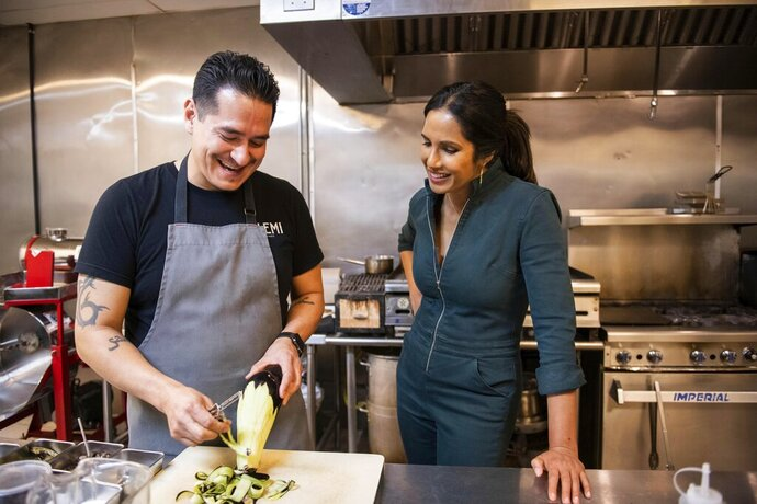 In this image released by Hulu, Emiliano Marentes, left, owner of Elemi, appears in his kitchen as host Padma Lakshmi looks on, in a scene from