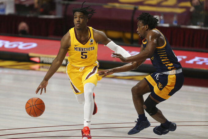 Minnesota guard Marcus Carr (5) handles the ball against UMKC guard Franck Kamgain (11) during an NCAA college basketball game Thursday, Dec. 10, 2020, in Minneapolis. (AP Photo/Stacy Bengs)