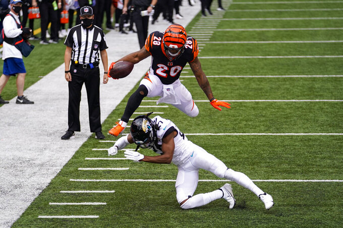 Cincinnati Bengals running back Joe Mixon (28) leaps over Jacksonville Jaguars cornerback Chris Claybrooks (27) for a touchdown in the first half of an NFL football game in Cincinnati, Sunday, Oct. 4, 2020. (AP Photo/Bryan Woolston)