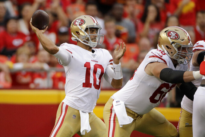 San Francisco 49ers quarterback Jimmy Garoppolo (10) throws a pass behind offensive guard Mike Person (68) during the first half of an NFL preseason football game against the Kansas City Chiefs in Kansas City, Mo., Saturday, Aug. 24, 2019. (AP Photo/Charlie Riedel)