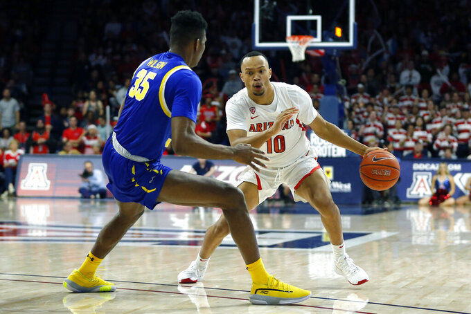 Arizona guard Jemarl Baker Jr. (10) drives against South Dakota State forward Douglas Wilson (35) in the second half during an NCAA college basketball game, Thursday, Nov. 21, 2019, in Tucson, Ariz. (AP Photo/Rick Scuteri)