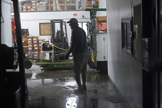 Steven Voisin walks through his family's heavily damaged oyster processing plant, as rain from Tropical Storm Nicholas, currently in the Gulf of Mexico, comes down through a destroyed roof, in the aftermath of Hurricane Ida in Houma, La., Tuesday, Sept. 14, 2021. (AP Photo/Gerald Herbert)
