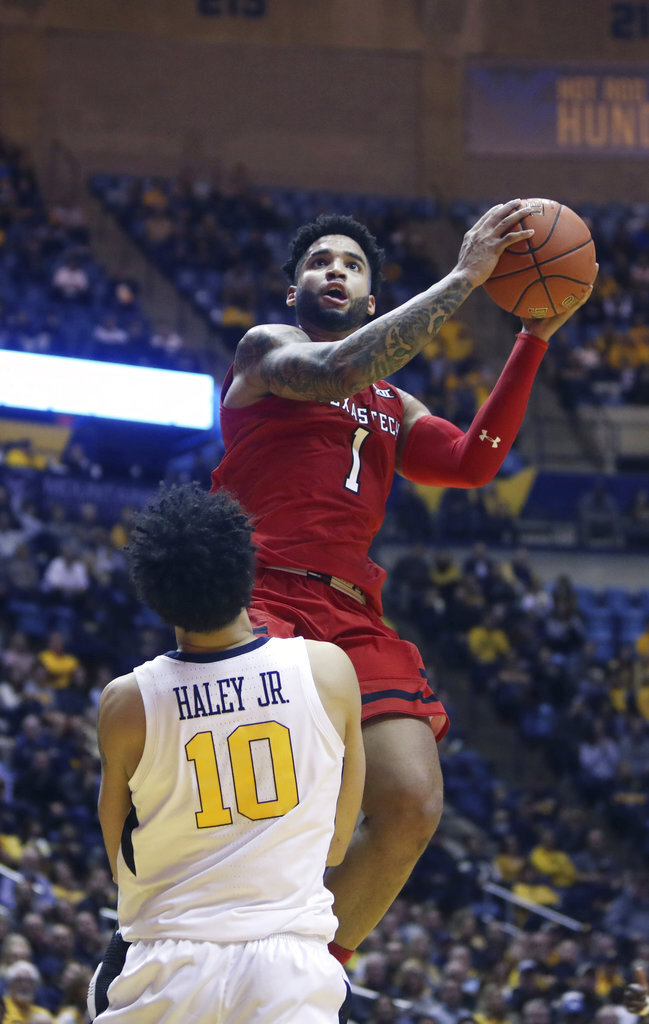 Texas Tech guard Brandone Francis (1) drives as West Virginia guard Jermaine Haley (10) attempts to draw a foul during the first half of an NCAA college basketball game Wednesday, Jan. 2, 2019, in Morgantown, W.Va. (AP Photo/Raymond Thompson)
