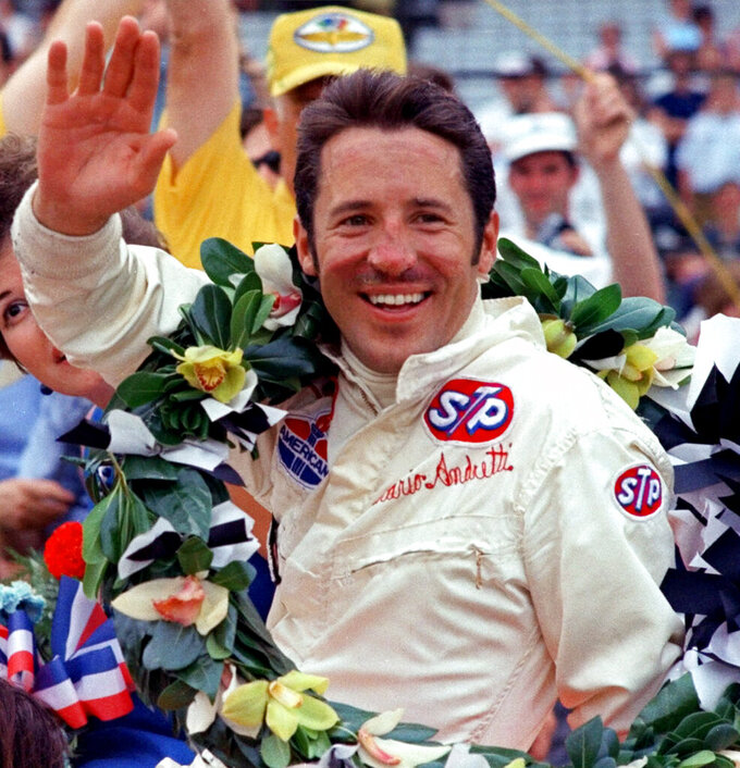 "FILE - In this May 30, 1969, file photo, Mario Andretti waves from the winner's circle after his victory in the Indianapolis 500 auto race at Indianapolis Motor Speedway in Indianapolis. Organizers announced Thursday, March 26, that the 500 would move from its traditional Memorial Day weekend slot to Aug. 23. ""It's a lot better than the word canceling,"" Andretti told The Associated Press. ""I think the postponement is something everyone was realistically expecting and at least it's something to shoot at. To me that's encouraging, it's something we all need while we're hunkered down, staring at the ceiling."" (AP Photo, File)"