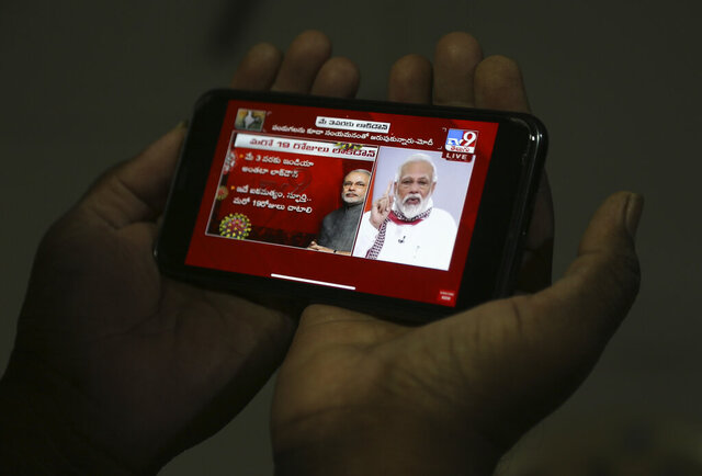 A man in Hyderabad, India watches on his mobile phone Prime Minister Narendra Modi address the nation in a televised speech about COVID-19 situation, Tuesday, April 14, 2020. Modi has extended the world's largest coronavirus lockdown hoping to head off the epidemic's peak as officials race to make up for lost time. (AP Photo/Mahesh Kumar A)