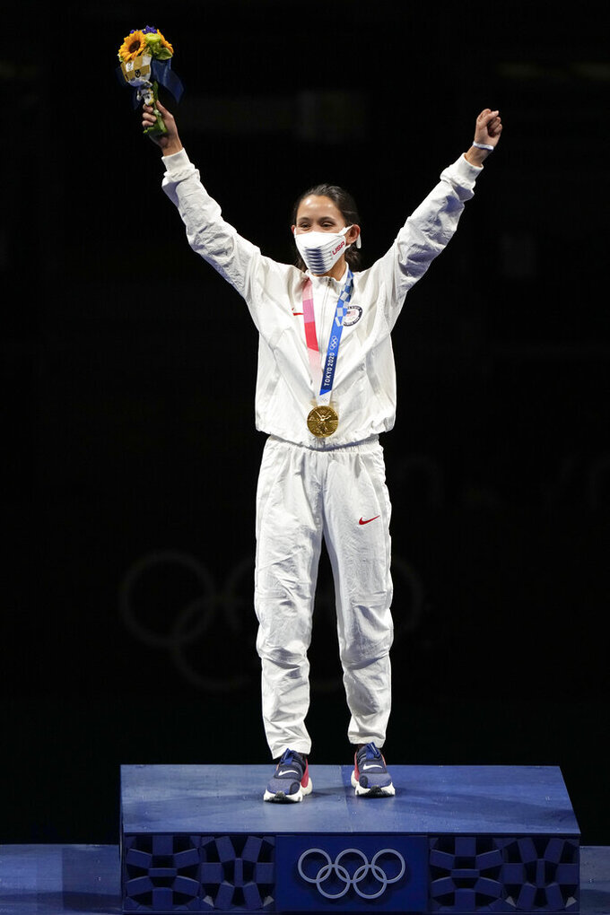 Lee Kiefer of the United States celebrates on the podium after winning the gold medal in the women's individual Foil final competition at the 2020 Summer Olympics, Sunday, July 25, 2021, in Chiba, Japan. (AP Photo/Andrew Medichini)
