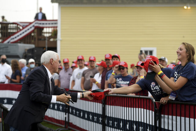 Vice President Mike Pence signs a hat for a supporter at a Republican campaign rally in Belgrade, Mont., on Monday, Sept. 14, 2020. (AP Photo/Tommy Martino)