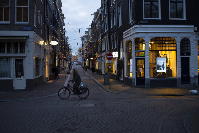 The capital's popular Nine Streets shopping area is near-deserted during lockdown in Amsterdam, Thursday, Jan. 14, 2021. The Dutch government this week extended by three weeks the tough lockdown in force since mid-December amid fears that coronavirus infection rates are not declining quickly enough and fears about a new more transmissible variant of the virus. (AP Photo/Peter Dejong)