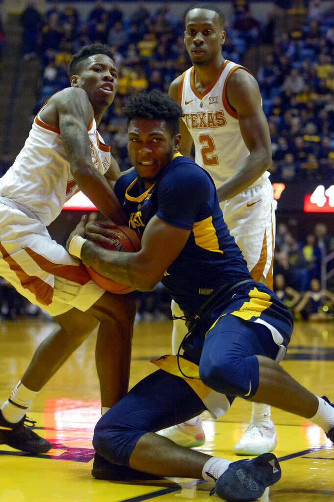 West Virginia forward Derek Culver, center, tries to keep his grip on the ball as Texas guard Kerwin Roach II (12) tries to take it during the second half of an NCAA college basketball game in Morgantown, W.Va. , Saturday, Feb. 9, 2019. (AP Photo/Craig Hudson)