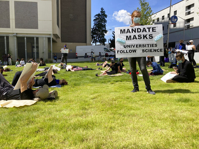 """Protesters call for Georgia university administrators to mandate masks and vaccination at a """"die-in"""" at Georgia State University, Thursday, Sept. 9, 2021, in Atlanta. Acting Chancellor Teresa MacCartney says the university system will not change its policy that restrains individual universities from requiring face coverings. (AP Photo/Jeff Amy)"""