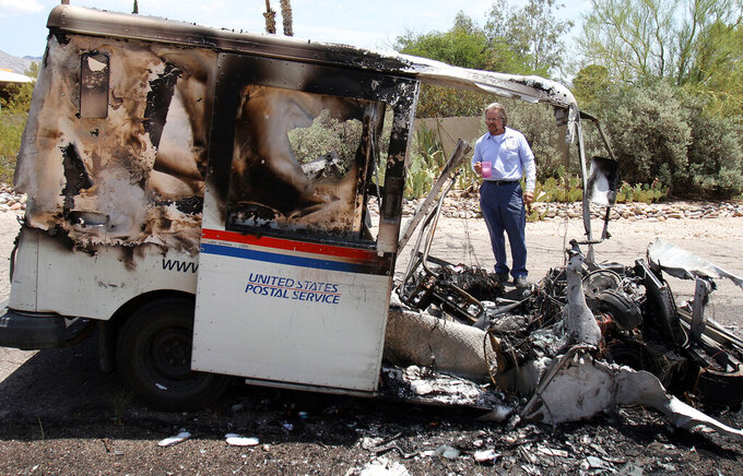 FILE - In this July 10, 2012 file photo, U.S. Postal Service Employee Brad Yonan surveys his 1993 Gramen postal vehicle after it caught fire as he tried to restart it while delivering mail north of Tucson, Ariz. The Postal Service's aging fleet of trucks is soldiering on even as a contract for greener replacement vehicles is being challenged. The primary fleet of vehicles that were delivered starting in 1987 is due to be replaced under a new contract, but the winning bid is being challenged. Hundreds of the aging trucks have been reported to catch fire in recent years. (David Sanders/The Arizona Republic via AP)