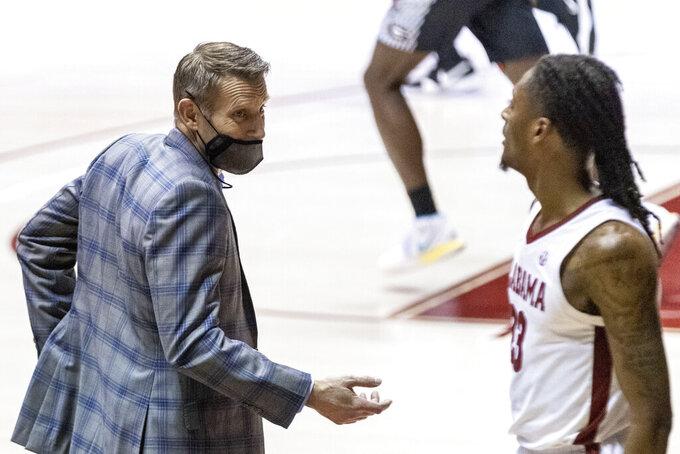 Alabama head coach Nate Oats talks with Alabama guard John Petty Jr. (23) during the second half of an NCAA college basketball game against Georgia on Saturday, Feb. 13, 2021, in Tuscaloosa, Ala. (AP Photo/Vasha Hunt)