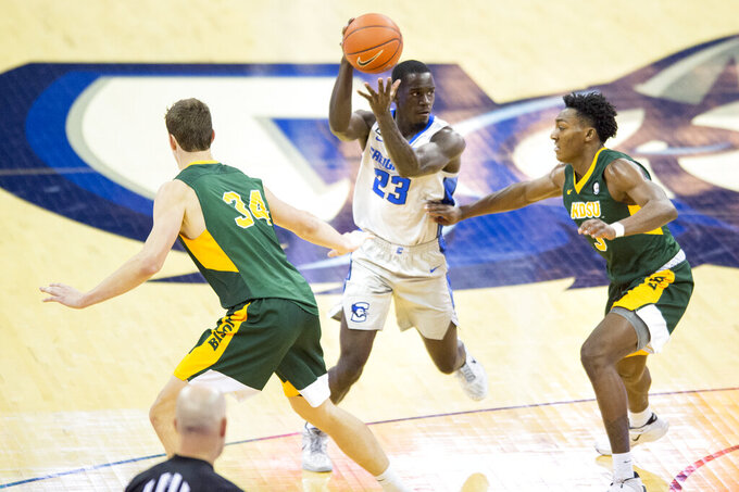Creighton's Damien Jefferson, center, drives through North Dakota State defenders Rocky Kreuser, left, Tyree Eady during the second half of an NCAA college basketball game in Omaha, Neb., Sunday, Nov. 29, 2020. (AP Photo/Kayla Wolf)