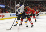 St. Louis Blues left wing Pat Maroon, left, fends off Chicago Blackhawks defenseman Carl Dahlstrom during the second period of an NHL hockey game Wednesday, April 3, 2019, in Chicago. (AP Photo/David Banks)