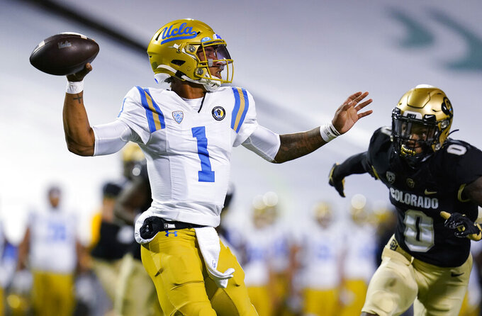 UCLA quarterback Dorian Thompson-Robinson, left, looks to throw the ball under pressure froim Colorado cornerback Chris Miller in the first half of an NCAA college football game Saturday, Nov. 7, 2020, in Boulder, Colo. (AP Photo/David Zalubowski)