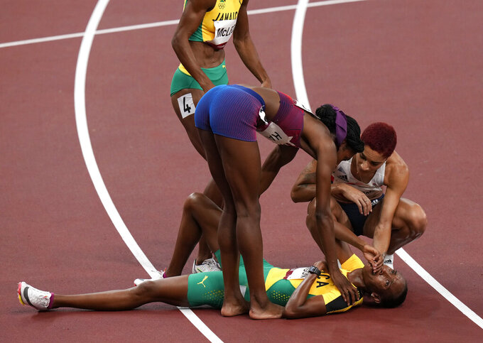 Stephenie Mcpherson, of Jamaica reacts as she is helped from the track after the final of women's 400-meters at the 2020 Summer Olympics, Friday, Aug. 6, 2021, in Tokyo, Japan. (AP Photo/Francisco Seco)