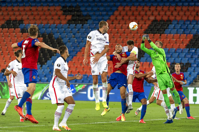 Frankfurt's goalkeeper Kevin Trapp, right, saves the ball, during the Europa League round of sixteen second leg soccer match between Switzerland's FC Basel 1893 and Germany's Eintracht Frankfurt at the St. Jakob-Park stadium in Basel, Switzerland, Thursday, Aug. 6, 2020. (Georgios Kefalas/Keystone via AP)