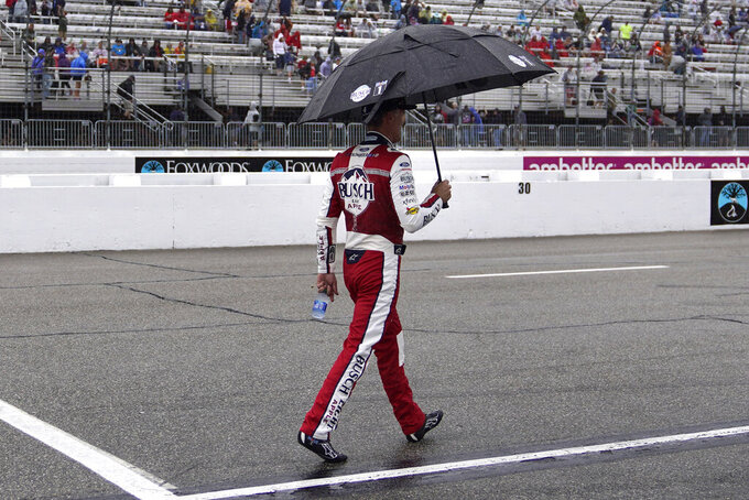 Kevin Harvick walks down pit road under an umbrella during a rain delay in the NASCAR Cup Series auto race Sunday, July 18, 2021, in Loudon, N.H. (AP Photo/Charles Krupa)