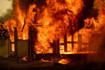 Flames from the Morton Fire consume a home near Bundanoon, New South Wales, Australia, on Thursday, Jan. 23, 2020. (AP Photo/Noah Berger)