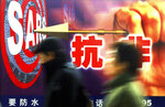 FILE - In this Dec. 18, 2003, file photo, people walk past a local government 's anti-SARS advertisement in Shanghai, China. Nearly two decades after the disastrously-handled SARS epidemic, China's more-open response to a new virus signals its growing confidence and a greater awareness of the pitfalls of censorship, even while the government is as authoritarian as ever. Chinese characters on the advertisement says