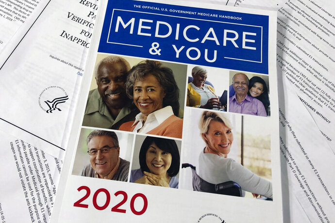 The Official U.S. Government Medicare Handbook for 2020 over pages of a Department of Health and Human Services, Office of the Inspector General report, are shown, Thursday, Feb. 13, 2020 in Washington.  A government watchdog tells The Associated Press it will launch a nationwide audit that may shed light on how seniors' personal Medicare information is getting to telemarketers, raising concerns about fraud and waste. An official with the Health and Human Services inspector general's office says the audit will be announced next week.  (AP Photos/Wayne Partlow)