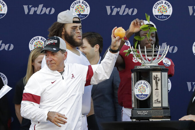 Alabama head coach Nick Saban, left, tosses citrus fruit to his players as they celebrate their victory over Michigan in the Citrus Bowl NCAA college football game, Wednesday, Jan. 1, 2020, in Orlando, Fla. (AP Photo/John Raoux)