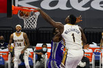 New Orleans Pelicans forward Zion Williamson, right, dunks over Sacramento Kings forward Chimezie Metu during the first quarter of an NBA basketball game in Sacramento, Calif., Sunday, Jan.17, 2021. (AP Photo/Rich Pedroncelli)