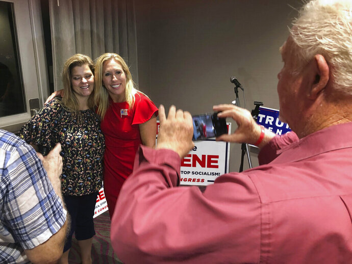 Supporters take photos with construction executive Marjorie Taylor Greene, background right, late Tuesday, Aug. 11, 2020, in Rome, Ga. Greene, criticized for promoting racist videos and adamantly supporting the far-right QAnon conspiracy theory, won the GOP nomination for northwest Georgia's 14th Congressional District. (AP Photo/Mike Stewart)