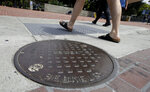 Pedestrians walk past a manhole cover for a sewer in Berkeley, Calif., Thursday, July 18, 2019. Soon students in Berkeley, California will have to pledge to