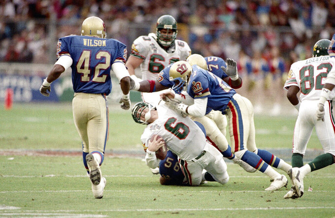 FILE - In this file photo dated June 9, 1991, Barcelona Dragons quarterback Scott Erney (6), is pulled to the ground after he was sacked by London Monarchs' Corris Ervin, right, and Roy Hart (75) in the second quarter of action in their World League Football Championship, World Bowl, game in London. The 2021 year marks the 30th anniversary of the World League of American Football. (AP Photo/Mike Feldman, FILE)
